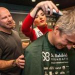Chris Lynch (left) watched as Miss Massachusetts USA shaved a participant?s head during a fundraiser for St. Baldrick?s Child Cancer Research.